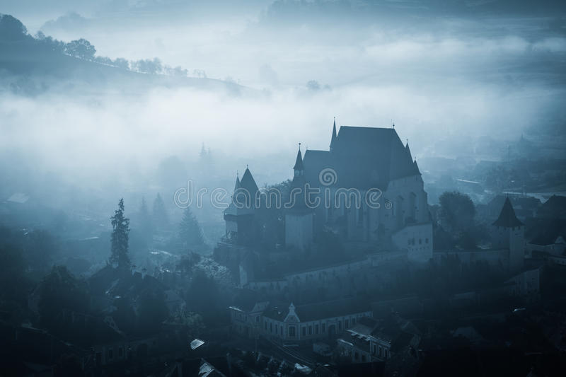 Mysterious misty morning over Biertan village, Transylvania, Romania. Blue colors. Halloween postcard concept stock image