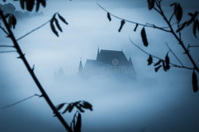 Mysterious misty morning over Biertan village, Transylvania, Romania. Blue colors. Halloween postcard concept royalty free stock photos