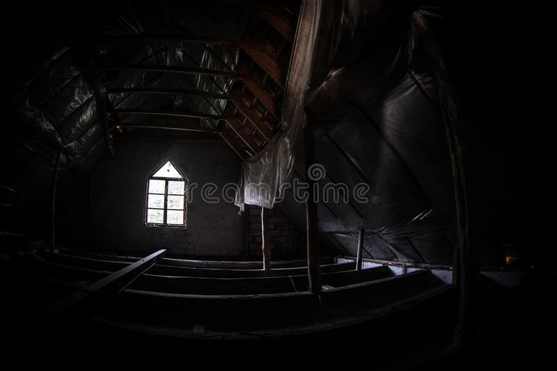 Mysterious mood created by white light in the window, subtle illuminated floor and total darkness around. Or Empty room with dramatic light entering the window royalty free stock images