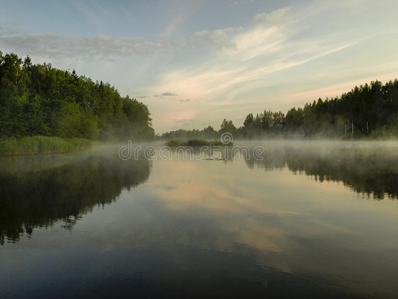 A mysterious morning on the lake, water like a mirror. White mist, lovely reflections, latvia stock photo