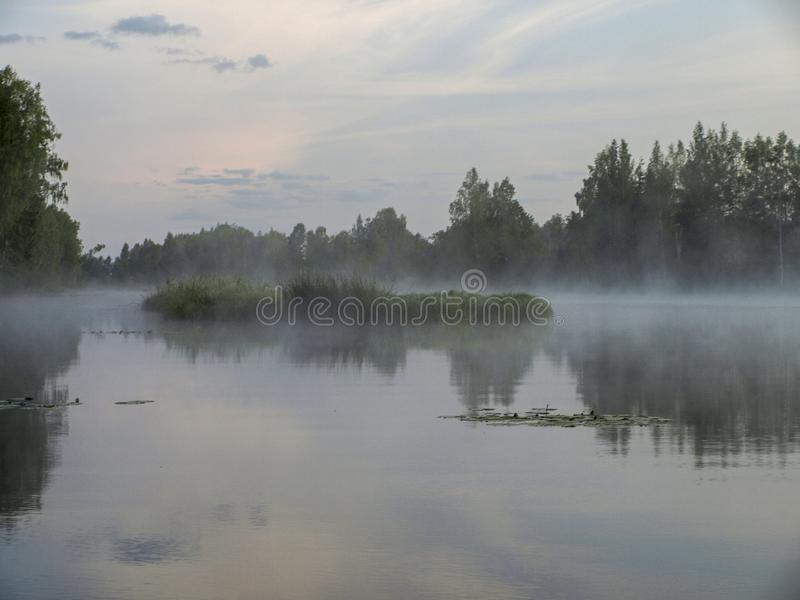 A mysterious morning on the lake. Water like a mirror, white mist, lovely reflections, latvia royalty free stock photo