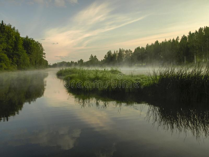 A mysterious morning on the lake, water like a mirror, white mist. Lovely reflections, latvia stock photos