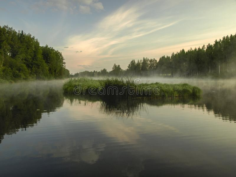 A mysterious morning on the lake, water like a mirror. White mist, lovely reflections, latvia stock photography