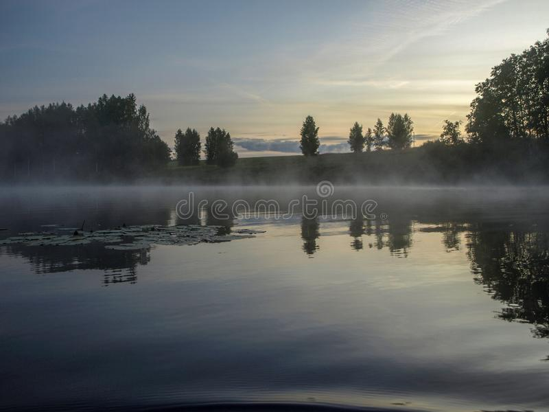 A mysterious morning on the lake, water like a mirror, white mist. Lovely reflections, latvia royalty free stock photography