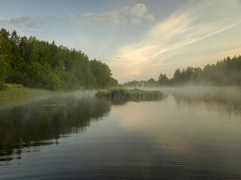 A mysterious morning on the lake, water like a mirror, white mist. Lovely reflections, latvia royalty free stock image