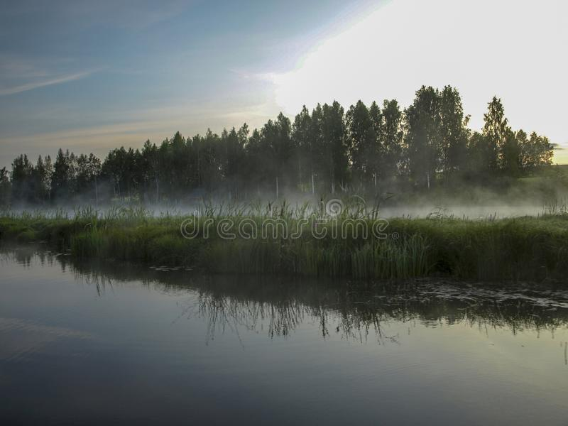 A mysterious morning on the lake, water like a mirror, white mist. Lovely reflections, latvia royalty free stock photo