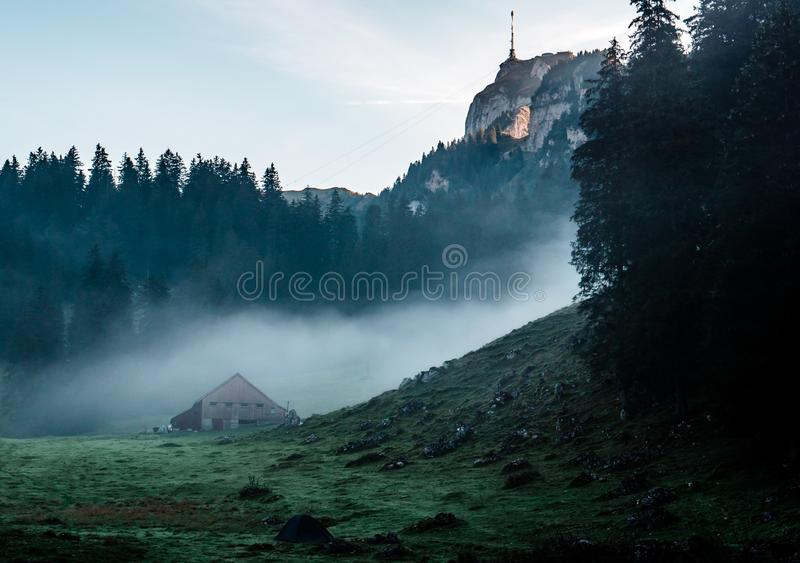 Mysterious mountain hut and tent during morning sunrise with fog stock photography