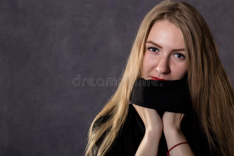Mysterious pretty blonde woman wearing black knitted sweater. Melancholy and autumn concept. on a gray background royalty free stock photo