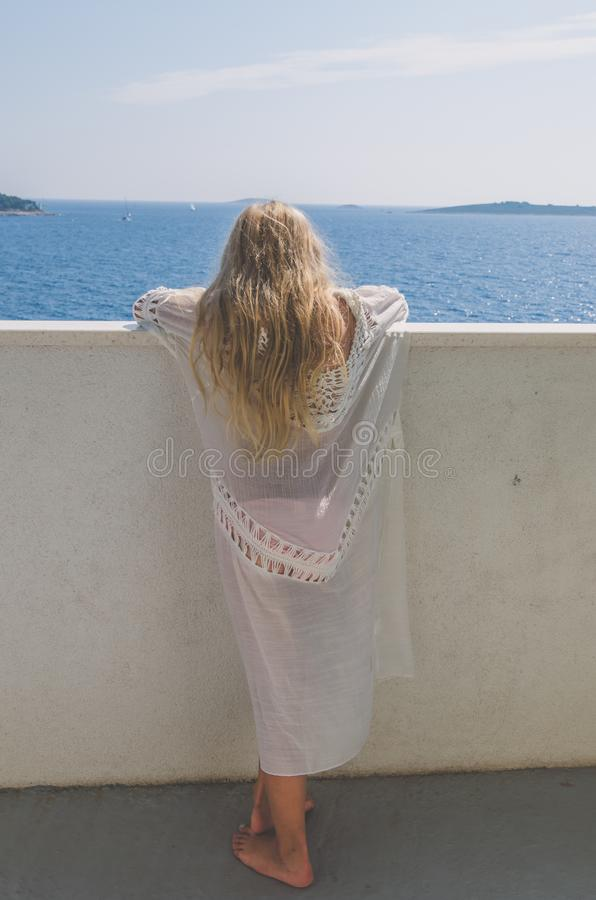 Mysterious princess with long blond hair looking from the balcony back view royalty free stock photo