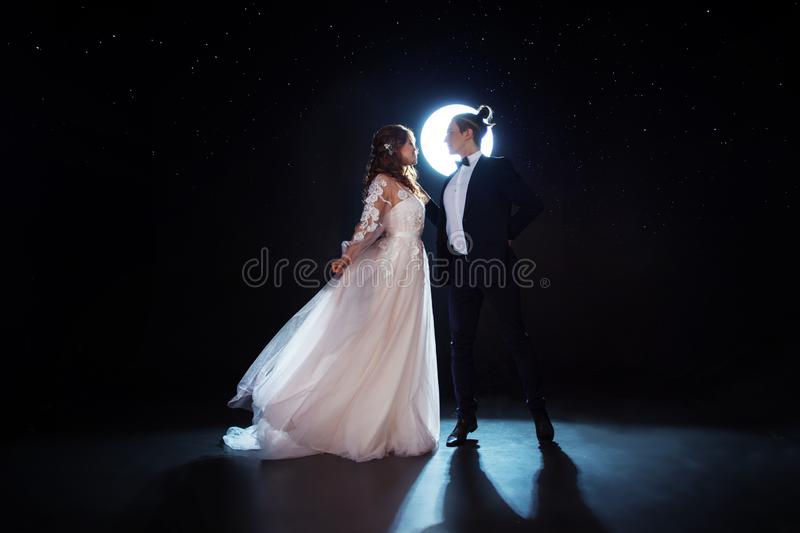 Mysterious and romantic meeting, the bride and groom under the starry sky. Hugs together. Man and woman, wedding dress. Dark background stock photography