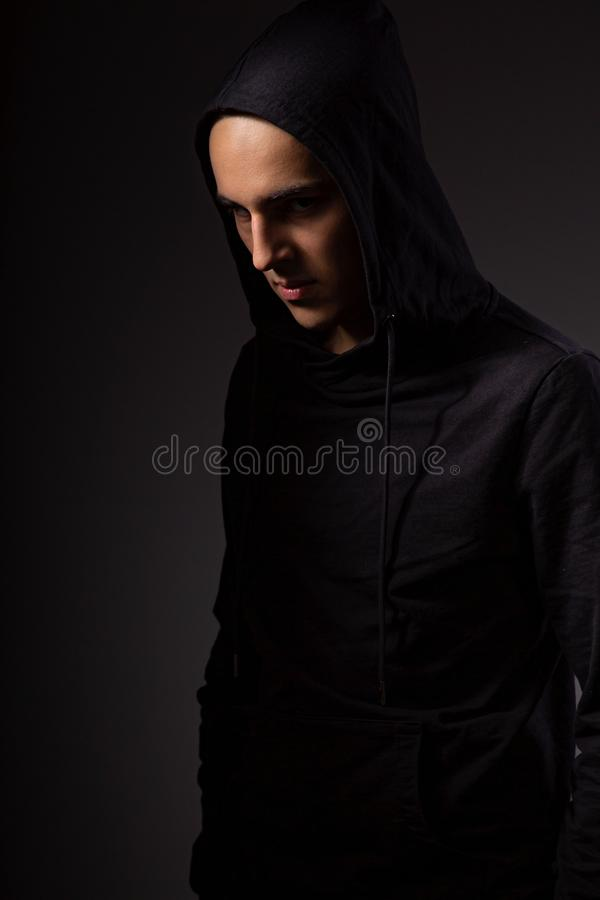 Mysterious serious man in black hoodie with hood on the head on dark background. Dangerous criminal person in dark shadow. Black and white royalty free stock photography