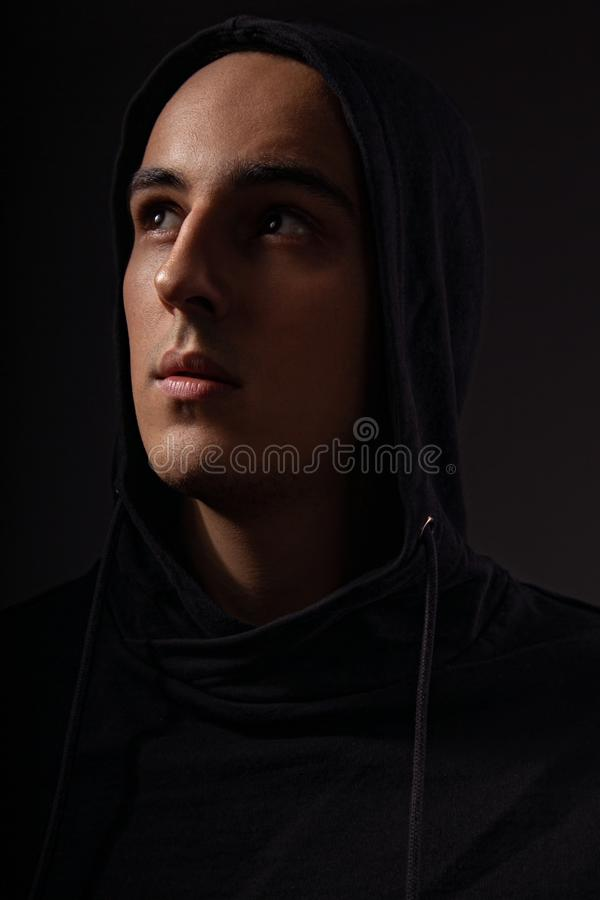 Mysterious serious man in black hoodie with hood on the head looking up on dark background. Dangerous criminal person stock image