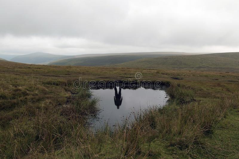 A mysterious silhouette of a man reflected in water with no one above on a bleak moorland hillside stock photography