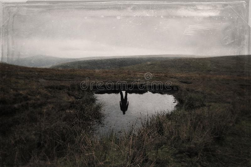A mysterious silhouette of a man reflected in water with no one above on a bleak moorland hillside. With a retro, grunge, blurred royalty free stock image