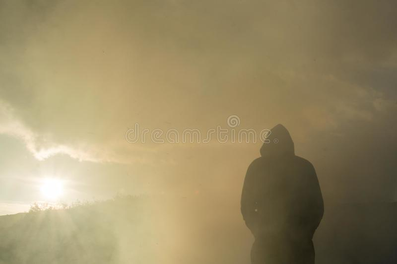A mysterious, silhouetted, hooded figure looking at the sunset, through smoke as ash falls from the sky.  stock images