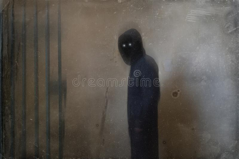 A mysterious spooky hooded figure with glowing eyes standing inside. With an artistic, blurred, weathered, textured edit.  stock images