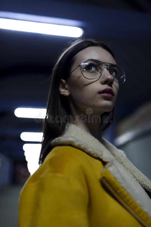 Mysterious stylish brunette in jacket and glasses, posing for womenswear fashion. City lights by night royalty free stock photography