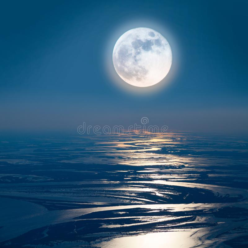 Lunar path on the lowland of Great river, top view. Mysterious Super moon over the floodplain of the Great River during spring flooding, aerial view royalty free stock photo