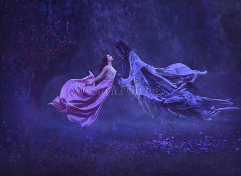 The mysterious witch is dancing with a demon, dark forces, in the air. Kiss dementor. Taking away the soul. A dress royalty free stock photo