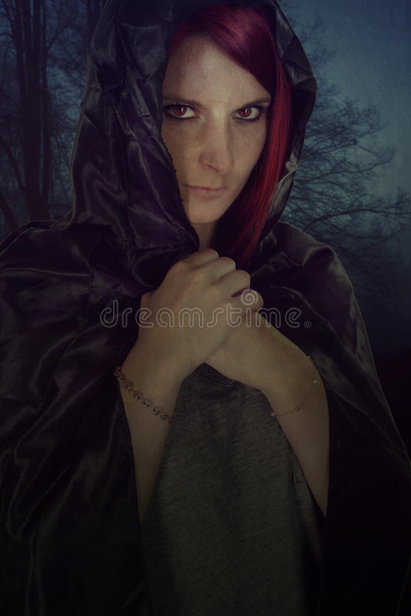 Mysterious witch in the woods. Mysterious witch hiding under her cape in the woods royalty free stock image