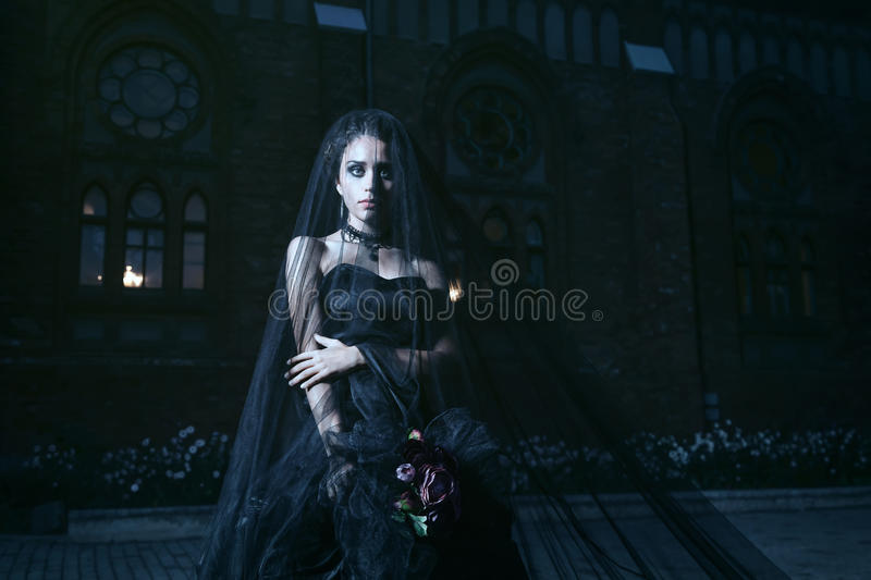Mysterious woman in black dress near chirch royalty free stock image
