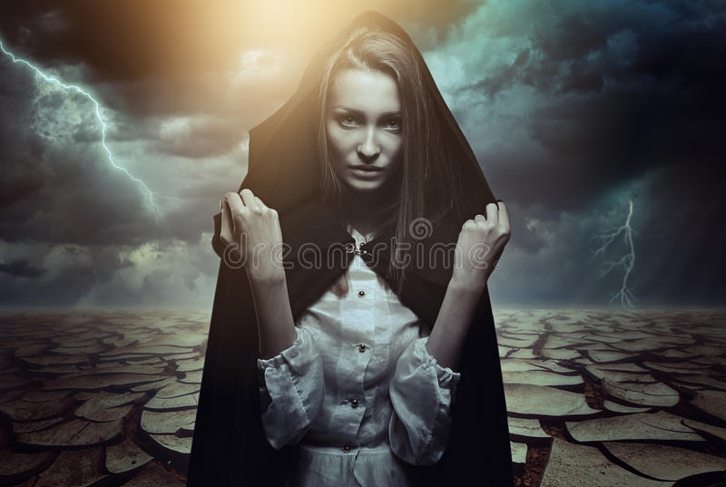 Mysterious woman in a desert landscape. Mysterious beautiful woman in a desert landscape. Fantasy and surreal royalty free stock photo