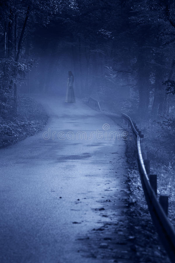 Mysterious Woman Ghost in White Dress. In the Misty Forest Road, vintage noise filter stock image