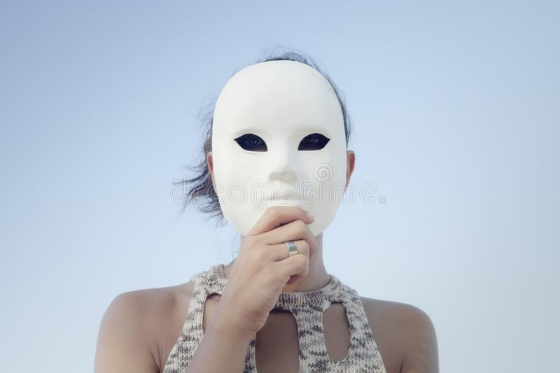 Mask secret girl blue sky. A mysterious woman hiding her face behind a plain white mask. Close-up symbolic shot. Outdoors, blue sky. Secrets, mystery royalty free stock photos