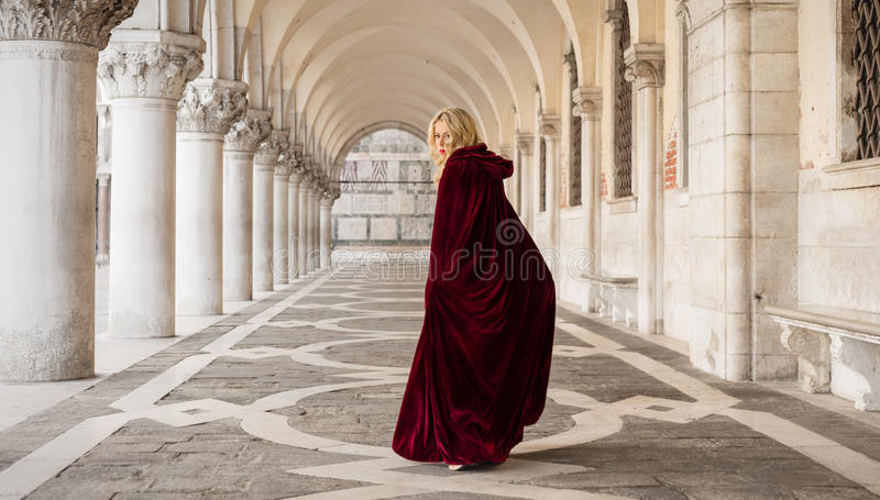 Mysterious woman in red cloak stock image