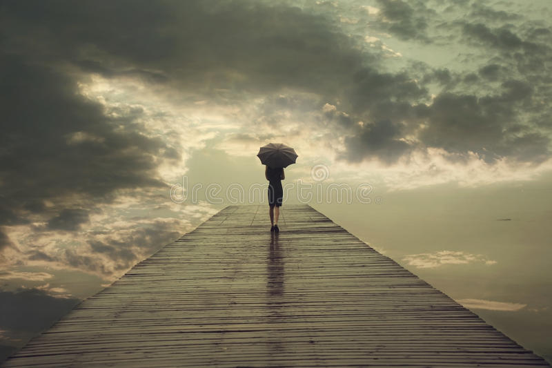 Mysterious woman with umbrella crosses a bridge to the threatening sky. Solitary woman with umbrella crosses a bridge to the threatening sky royalty free stock photo