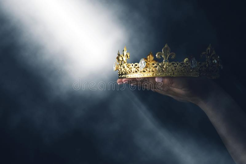 Mysteriousand magical image of woman`s hand holding a gold crown over gothic black background. Medieval period concept. Mysteriousand magical image of woman`s royalty free stock photos