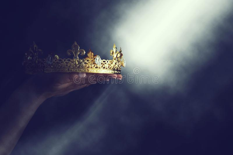 Mysteriousand magical image of woman`s hand holding a gold crown over gothic black background. Medieval period concept. royalty free stock photos