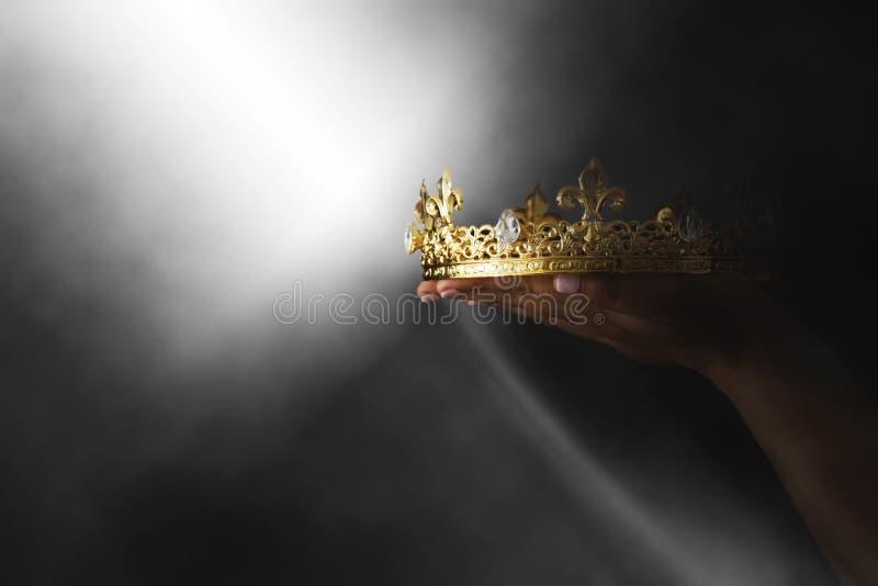 Mysteriousand magisk bild av handen för kvinna` som s rymmer en guld- krona över gotisk svart bakgrund medeltida periodbegrepp arkivbilder