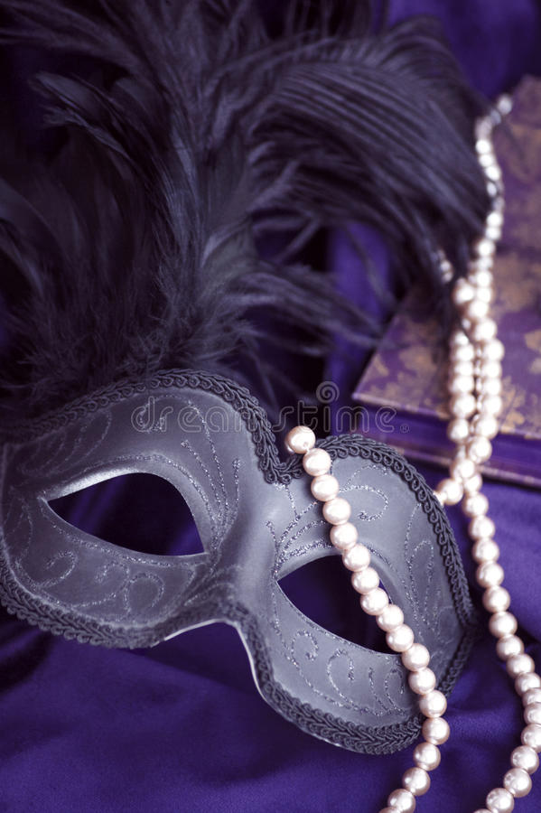 Mystery. Carnival mask, a pearl necklace and a book on purple velvet royalty free stock image