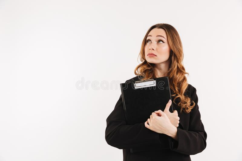 Mystery elegant woman in coat holding clipboard and looking up stock images