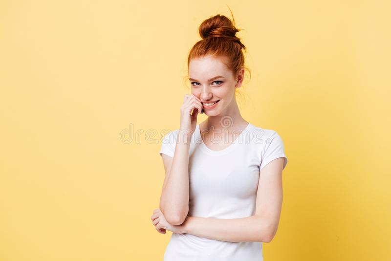 Mystery ginger woman in t-shirt bites her finger royalty free stock images