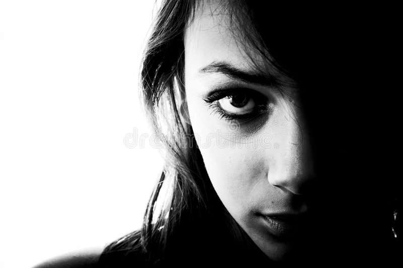Mystery girl. Black and white portrait in horizontal form of a mysterious looking teen girl, one side of her face in shadows royalty free stock photos