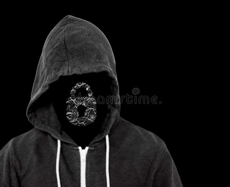 Mystery Hooded Computer Hacker Criminal. Hooded menacing man with unseen face wearing a black top with a computer lock which has been broken by the hackers stock photography