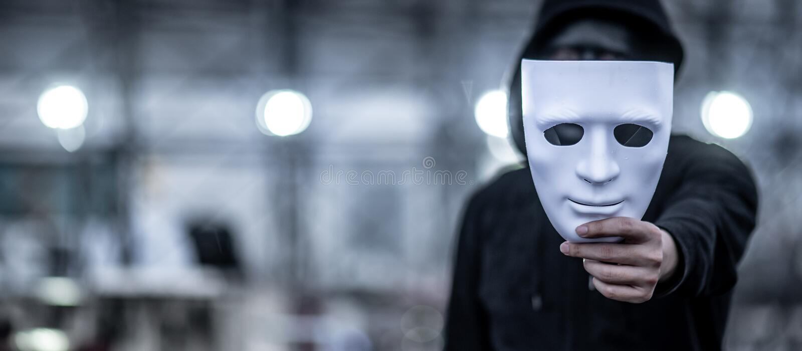 Mystery hoodie man holding white mask royalty free stock photos