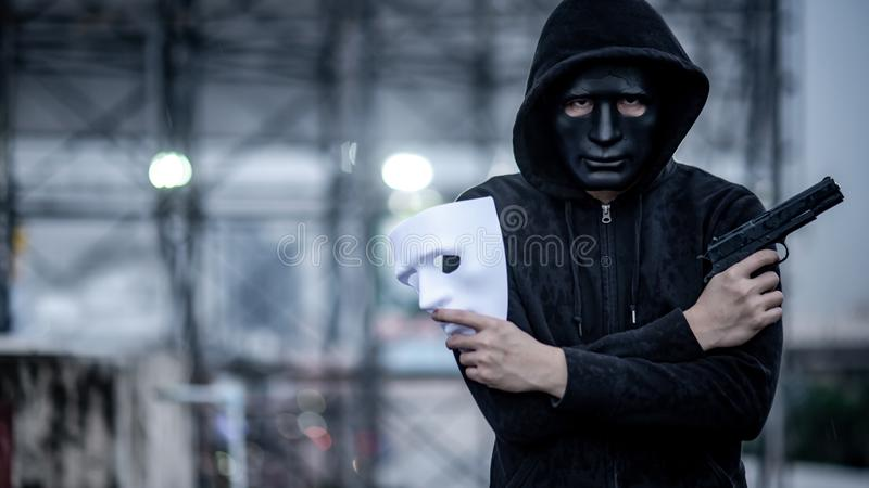 Mystery hoodie man holding white mask and gun royalty free stock images