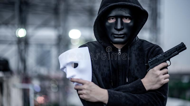 Mystery hoodie man with broken black mask holding white mask and gun. Crime and violence concepts stock images