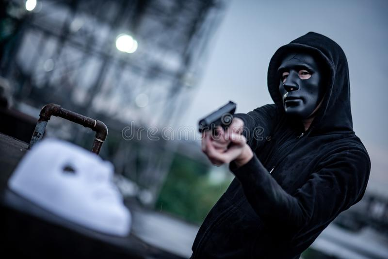 Mystery hoodie man in broken black mask pointing gun at white mask. Crime and violence concepts stock photo