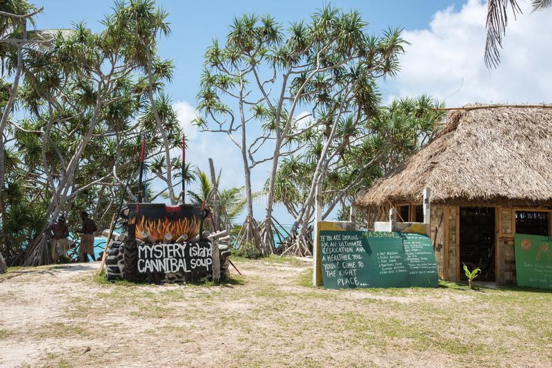 Mystery Island Cannibal Soup. MYSTERY ISLAND, VANUATU, PACIFIC ISLANDS: DECEMBER 2,2016: Thatched roof structure with signs, people, humorous cannibal soup royalty free stock photo