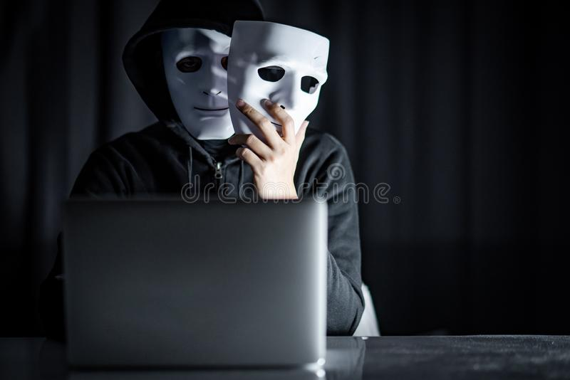 Mystery male hacker holding white mask royalty free stock photography
