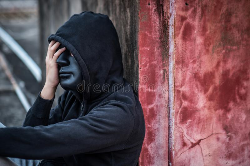 Mystery man with black mask feeling stressed sitting in abandoned building stock image