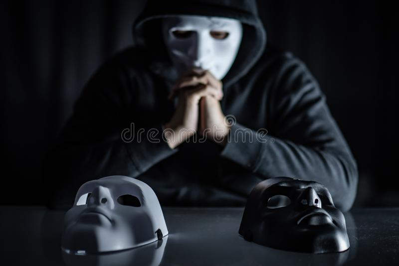 Mystery man choosing mask on the table. Hoodie man wearing mystery mask choosing black or white mask on the table. Anonymous social masking. Major depressive royalty free stock photos