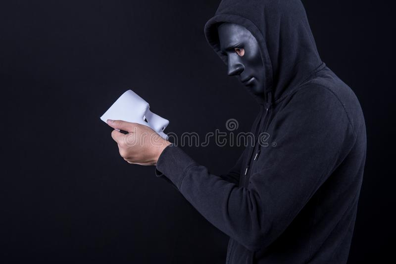Mystery man holding and looking at white mask royalty free stock image