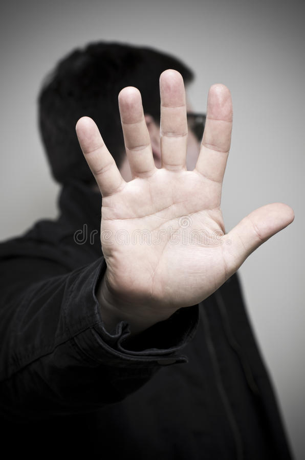 Mystery Man Holding Up Hand And Looking Away Stock Image