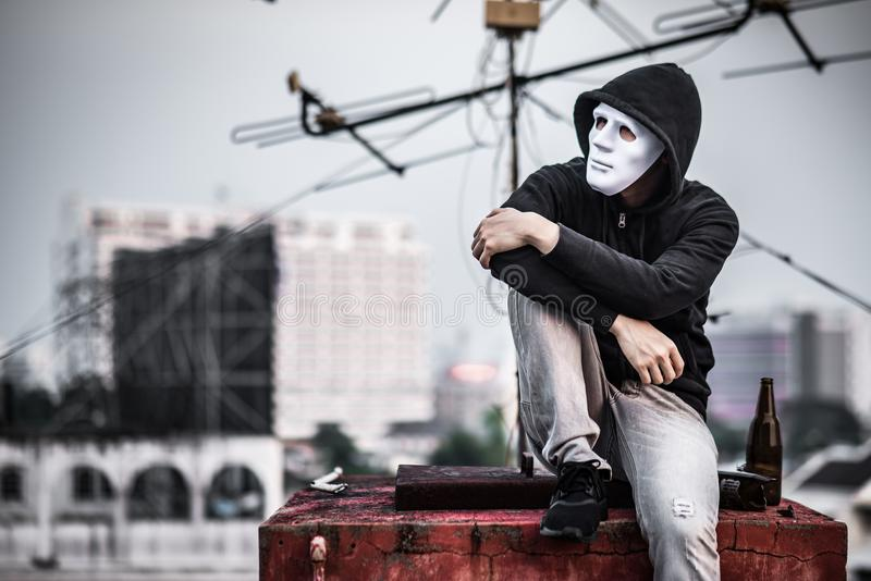 Mystery man in the mask sitting with empty and broken bottle stock photo