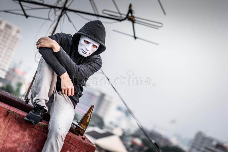 Mystery man in the mask sitting with empty and broken bottle. Mystery man in white mask with hoody jacket, sitting and hugs his knees up with broken empty bottle stock photos